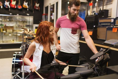 lady playing electronic drums with man collaborating