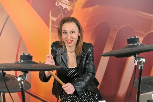lady wearing black leather jacket playing electronic drums