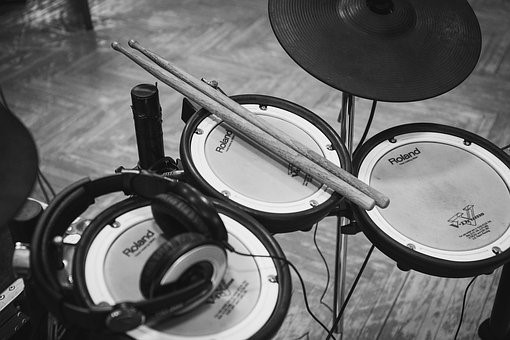 electronic drums with drumstick and headphone on top