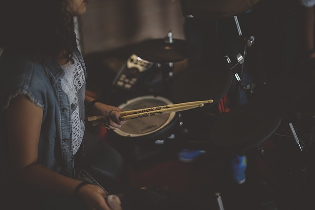 guy sitting and holding drumsticks on hand